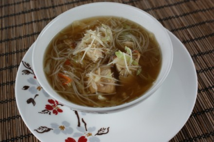 Asian chicken noodle soup with rice vermicelli noodles, carrots, cabbage, cole slaw, green onions, soy sauce, and chicken