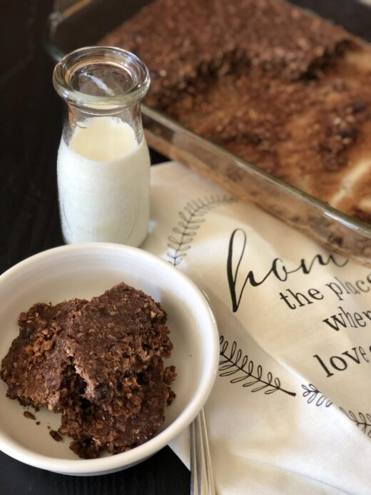 Double Chocolate Baked Oatmeal in white bowl with a glass of milk