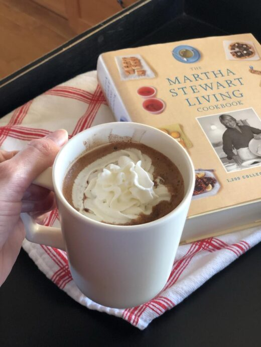 Martha Stewart's Hot Chocolate Recipe in mug with whipping cream and cookbook