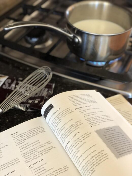 Cooking Martha Stewart's Hot Chocolate in a pan with Cookbook on counter