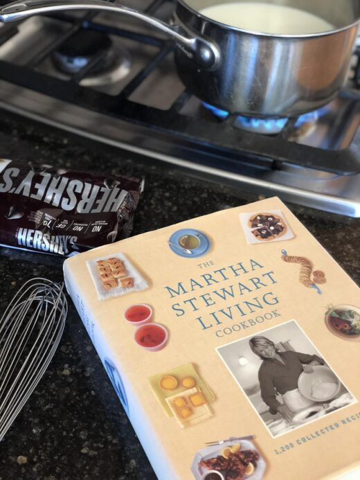 Cooking Martha Stewart's Hot Chocolate in pan with whisk and chocolate next to cookbook