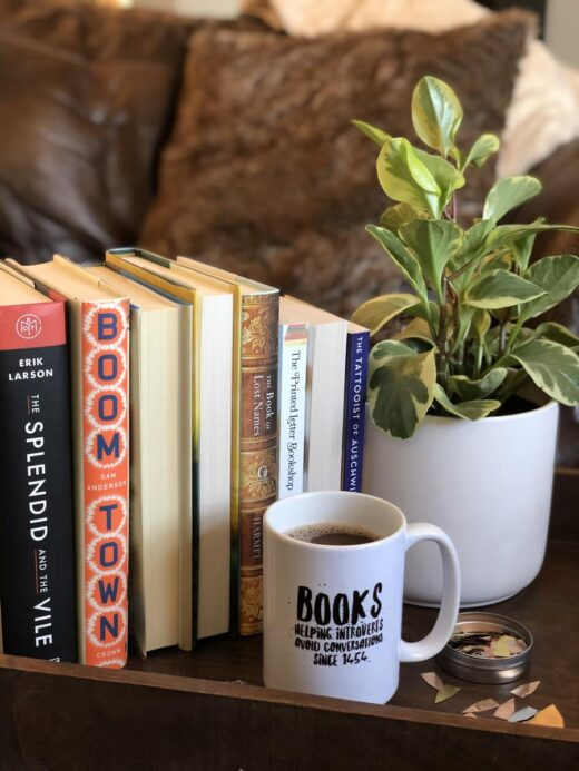 Books, Coffee, and a plant with couch in the background
