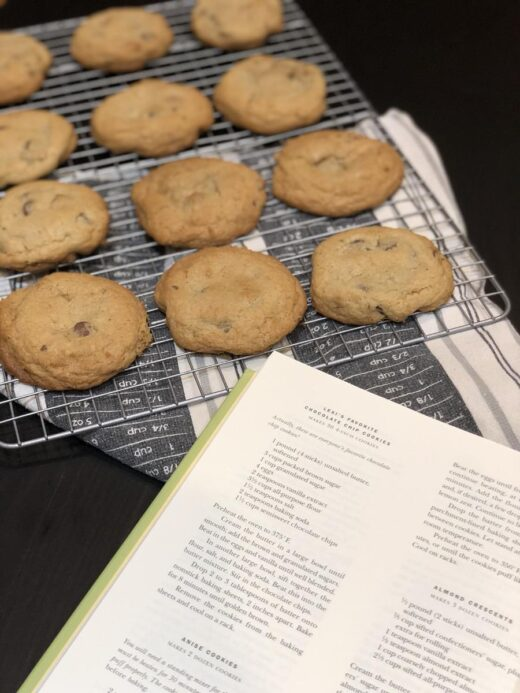 Chocolate Chip Cookies on a cooling rack next to a cookbook