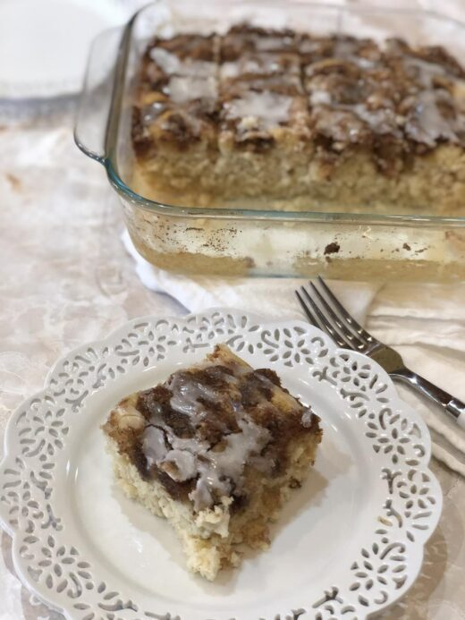 Cinnamon Roll Muffin Cake Gluten Free on white plate with cake in background